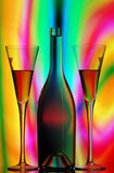 Design spirits. Still life with a bottle of champagne and flutes with vivid colorful abstract background Royalty Free Stock Photo