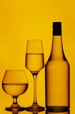 Liquor or wine bottle and glasses. Silhouetted bottle of liquor, wine glass and a cognac glass against dim lighted background Stock Photo