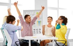 Happy creative team or designers at office. Design, success, business and people concept - happy creative team of interior designers celebrating triumph at royalty free stock image
