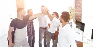 Design team giving each other a high five. The concept of teamwork stock photo