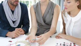 Design team looking at costume jewelry and speaking together Royalty Free Stock Photos