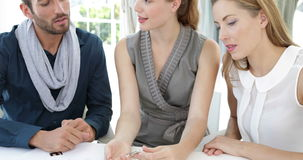 Design team looking at costume jewelry and speaking together Stock Image