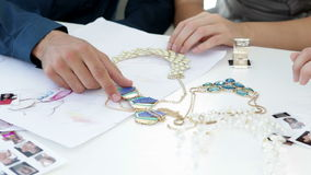 Design team looking at costume jewelry and talking Royalty Free Stock Photography