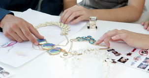 Design team looking at costume jewelry and talking Stock Image