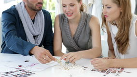 Design team looking at jewelry and talking Stock Image