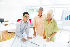 Design Team Planning on a New Project with their Blueprint.  stock images