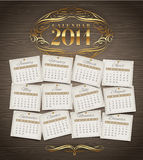 Design template - Calendar of 2014 with golden ornate elements. On a wooden background Stock Illustration