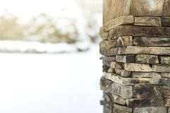 Design template for the greeting card on winter theme, column is constructed of stones on the foreground, snow environment on back Royalty Free Stock Photo