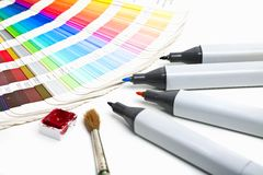 Design Tools. Color chart, pencils and cup of watercolor on white paper Royalty Free Stock Photography