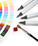 Design Tools. Color chart, pencils and cup of watercolor on white paper Stock Image