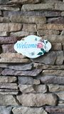 Design welcome sign. Flower design welcome sign on rock wall background wallpaper royalty free stock photography