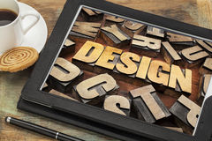 Design  word on digital tablet. Design word abstract in letterpress wood type on a digital tablet with cup of coffee Royalty Free Stock Image