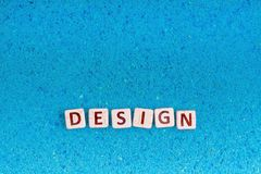 Design word on stone. Design word write in square white stone on blue sand, free space for your text stock images