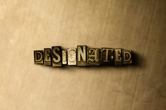 DESIGNATED - close-up of grungy vintage typeset word on metal backdrop Stock Photos