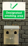Designated Smoking Area. A sign indicating that this location is a designated smoking area complete with cigarette receptacle Royalty Free Stock Images