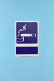 Designated smoking area sign on blue wall of a building Royalty Free Stock Images