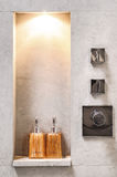Designed bathroom with raw concrete wall decorated with bottle s Stock Image