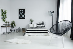 Designed black chair in modern bedroom. With black picture on white wall above king-size bed Stock Images