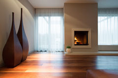 Designed decoration in living room. Burning fireplace and designed decoration in living room Royalty Free Stock Photo