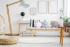 Designed lamp near beige sofa. With pillows in kid room with posters on white wall and pouf on floor Royalty Free Stock Photography