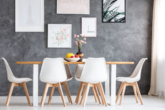 Designed loft with long table. Designed loft with long dining table with fruits in white bowl and pink flowers in dark vase Royalty Free Stock Images