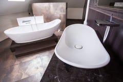 Designed washbasin and bathtub. In luxury bathroom stock photos