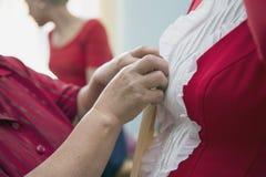 Designer adjusting dress on model Stock Images