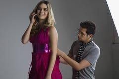 Designer Adjusting Dress On Model Stock Photos