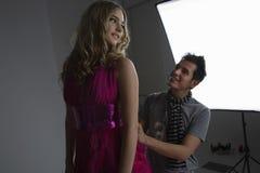 Designer Adjusting Dress On Model Stock Photography