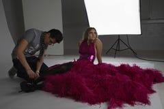 Designer Adjusting Shoe On Fashion Model Stock Photo