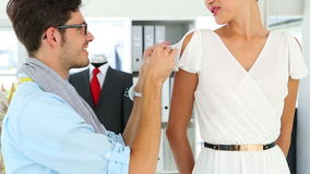 Designer adjusting sleeve of dress on model Stock Photos