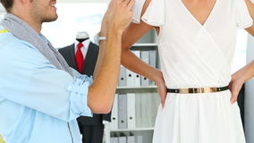 Designer adjusting sleeve of dress on model and smiling at camera Royalty Free Stock Images