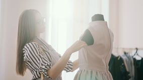 The designer adjusts the blouse on the mannequin. The designer adjusts the blouse on the mannequin stock footage