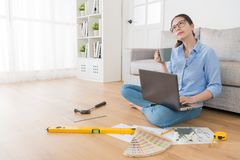 Designer adviser thinking how to remodel house. Beautiful elegant female designer adviser thinking how to remodel house and sitting on floor with many design Royalty Free Stock Photography
