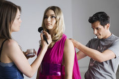 Designer And Artist Preparing Model For Photo Shoot Royalty Free Stock Photos