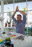 Designer with arms raised meditating while sitting at desk Stock Photos