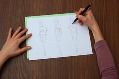 Designer assessing fashion drawings Royalty Free Stock Image