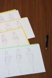 Designer assessing fashion drawings Stock Image