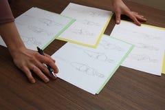 Designer assessing fashion drawings Stock Photos