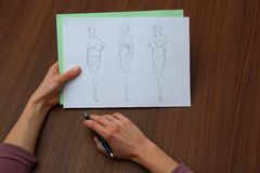 Designer assessing fashion drawings Royalty Free Stock Photos