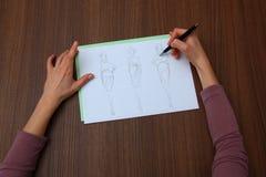 Designer assessing fashion drawings Stock Photo