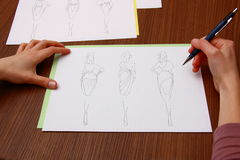 Designer assessing fashion drawings Stock Image