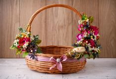 Designer basket is decorated with flowers. Wicker basket for celebrating Easter and other holidays. Stock Photo