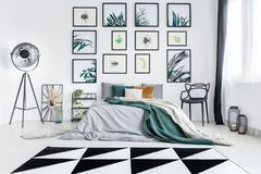 Designer bedroom with metal furniture. Geometric carpet in bright designer bedroom with metal furniture and green bedding on bed Royalty Free Stock Images