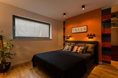 Designer bedroom with orange wall royalty free stock photo