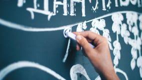 Designer bei der Arbeit: die Hand des Mädchens zeichnet eine Kreide auf einer Tafel stock footage