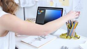 Designer betrachtet den Computer und wählt Schatten für eine neue Sammlung Kleidung vor stock video