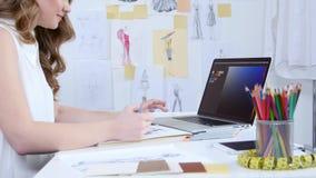 Designer betrachtet den Computer und wählt Schatten für eine neue Sammlung Kleidung vor stock video footage