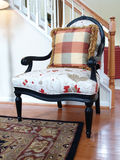 Designer Chair. An upholstered chair with ebony finish sitting in a modern foyer against the staircase Stock Photos
