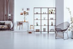 Designer chair in living room. Designer chair in spacious living room with decorations on shelves, beige sofa and table stock photography